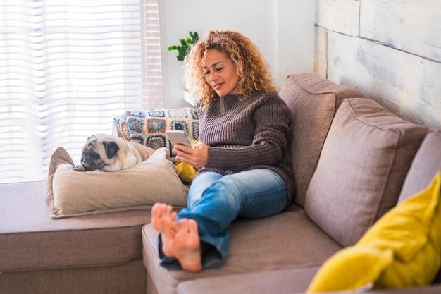 自宅で幸せな大人の美しい巻き毛の女性が、親友の犬のパグと一緒に携帯電話から入力して読書をしている