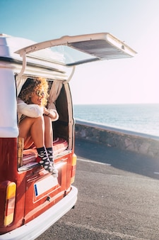 행복 한 성인 아름 다운 여자는 오래 된 빈티지 밴 전송 뒤에 앉아 도로와 바다를 찾고 여행 라이프 스타일이나 여름 휴가 휴가를 즐길 수