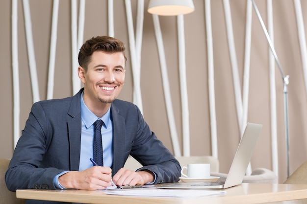 Happy adult businessman working at desk in office