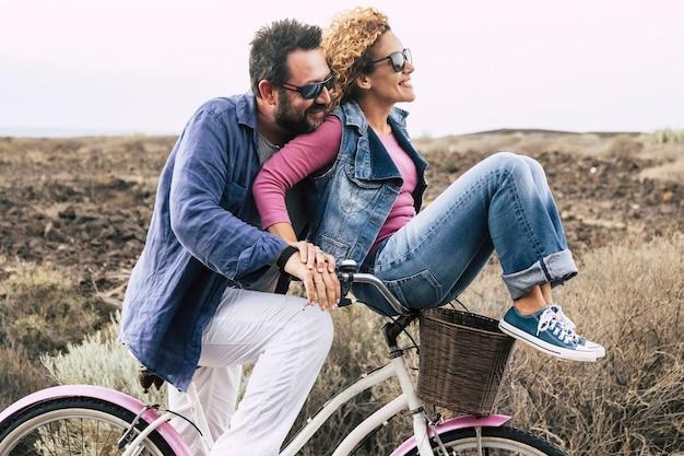 アウトドアレジャー活動で自転車を楽しんでいる幸せな大人の白人カップルアクティブな人々