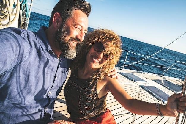 ヨットで一緒に幸せな大人の白人カップルは休暇をお楽しみください