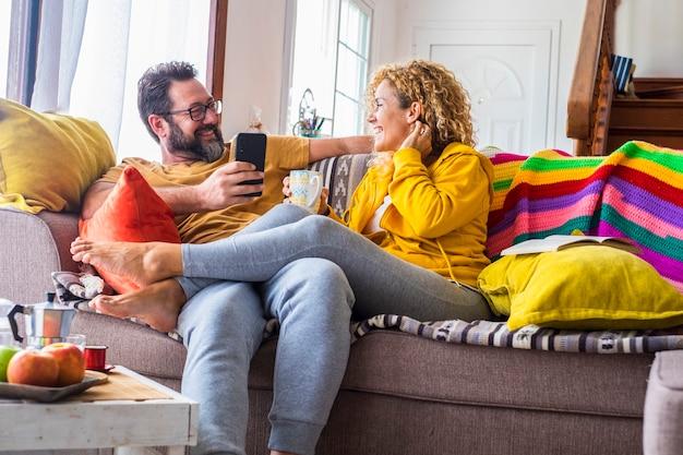 カラフルなカバー付きのソファに座って自宅で幸せな大人のカップルは、愛と関係のライフスタイルと一緒に笑顔と笑いで朝食の朝のレジャー活動をお楽しみください-日曜日の時間