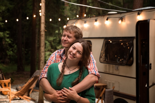 Happy adult couple blond man hugging pretty woman lives in trailer rv in summer vacation