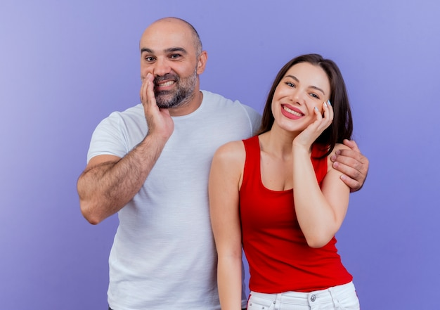 顔と男性の両方を見て、触れて幸せな大人のカップルが女性の肩に手を置く