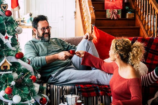 幸せな大人のカップルは楽しさと笑顔でクリスマスイブの朝を一緒に祝います。ソファに横になっている流行に敏感なひげを生やした男性と彼にコーヒーを与える妻の女性-家の装飾