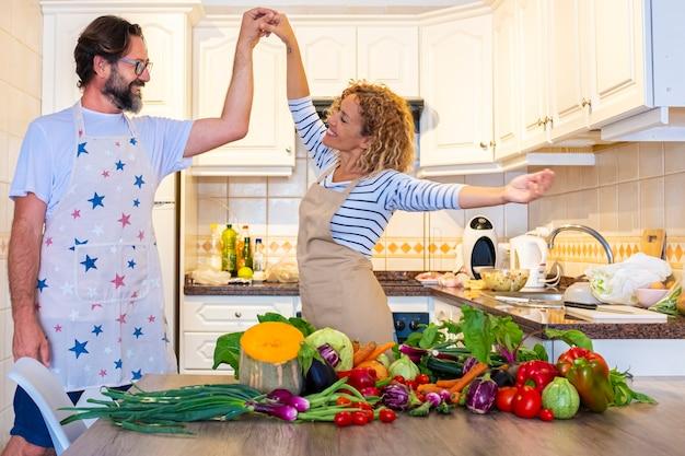 幸せな大人のカップルは、テーブルの上で健康的な野菜を準備しながら、自宅のキッチンで一緒に踊り、楽しんでください。大喜びの女性と恋愛中の男性が昼食を準備し、関係を楽しむ