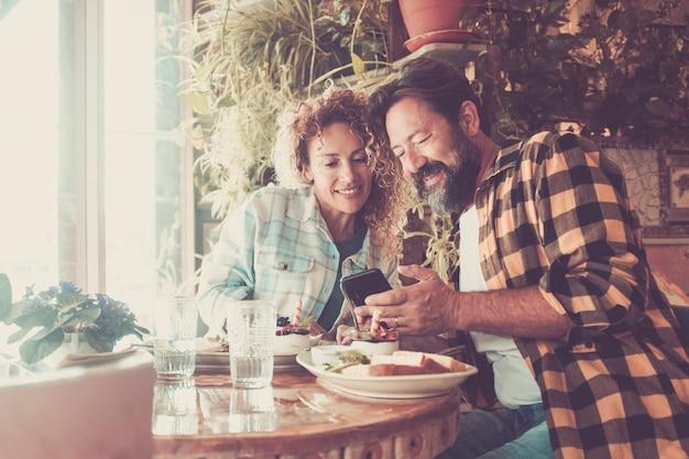 幸せな大人のカップルは、バーレストランの休憩を屋内で一緒に楽しんでいます。現代の携帯電話を使用して友人にビデオ通話をしたり、ウェブで探したりしています-オンラインの現代人のワイヤレス接続