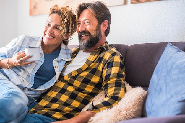 Happy adult couple enjoy home leisure activity together watching tv on the sofa - love and daily real relationship caucasian people indoor - man and woman enjoy time on the sofa with joyful
