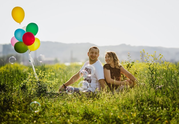 Happy adult couple has fun on a green field sitting with colorful balloons