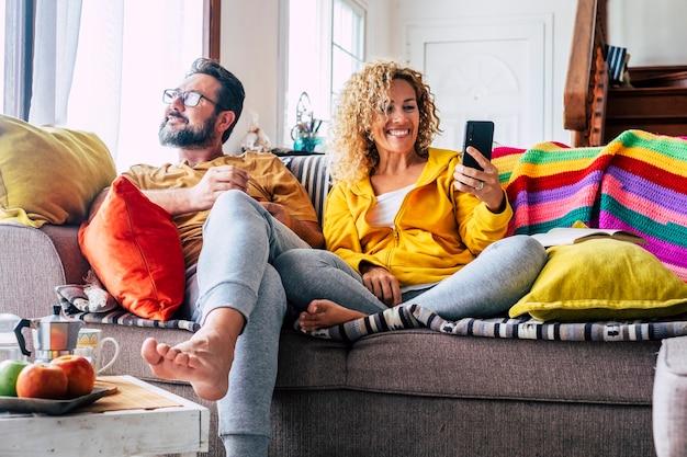 幸せな大人のカップルの男性と女性は朝の朝食で一緒に家で時間を楽しんでいます。電話を使用して窓の外を見る屋内レジャー活動における関係ライフスタイルの人々
