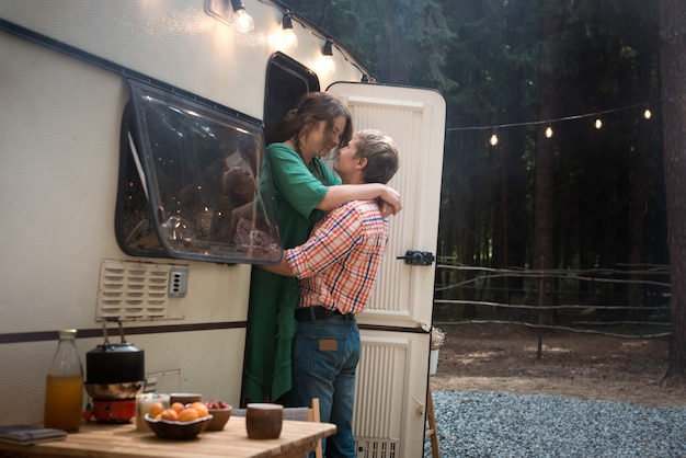 Happy adult couple man and woman living in trailer in forest at summer vacation