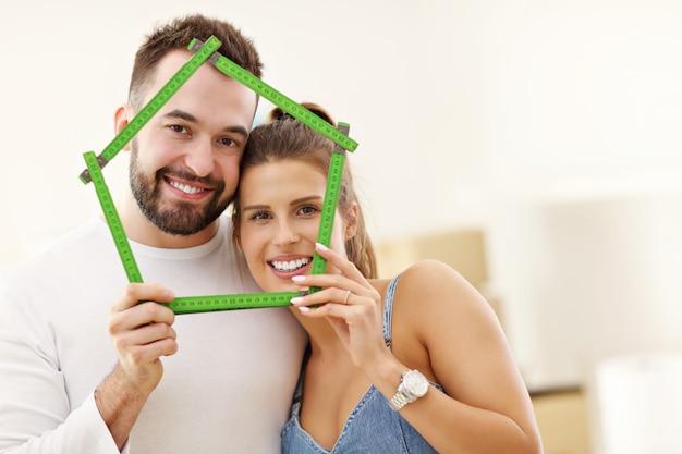 幸せな大人のカップルが新しい家に出入りする