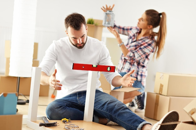 Счастливая пара взрослых пытается собрать мебель