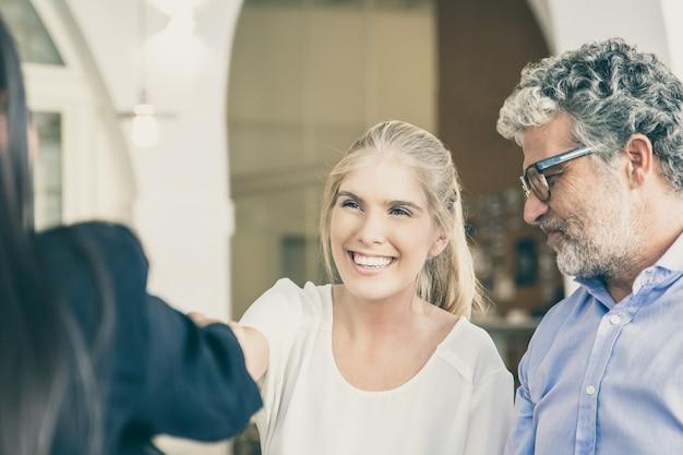 행복 한 성인 딸과 성숙한 아버지가 공동 작업에서 가족 컨설턴트와 회의, 악수