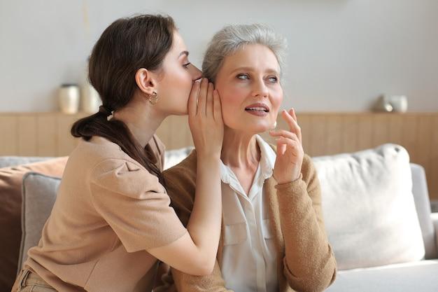 幸せな大人の娘が家で彼女の真ん中の母親に秘密をささやき、うわさ話をし、秘密を共有します。成熟したお母さん、信頼できる関係から良いニュースを聞いている美しい女性。