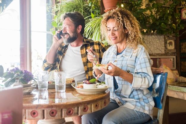 幸せな大人の男性と女性は、昼食のためにテーブルに座っているバーレストランで健康的な食べ物を一緒に食べる時間を楽しんでいます-流行に敏感な白人カップルは笑顔でお互いに時間を過ごします