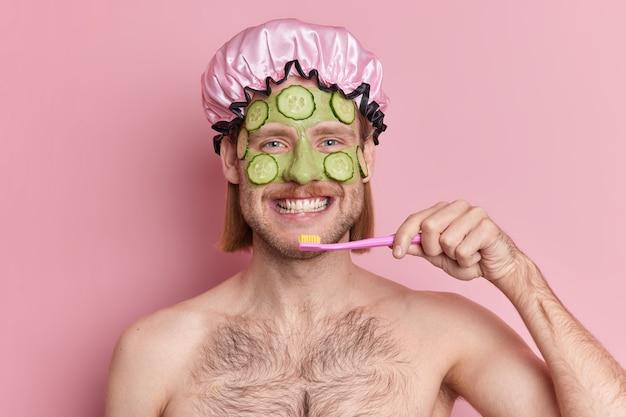 L'uomo adulto felice applica una maschera nutriente verde con fette di cetriolo sul viso, lava i denti con uno spazzolino da denti, sta mezzo nudo al coperto, ha routine igienica quotidiana mattutina.