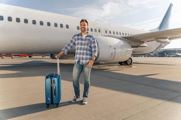 Счастливый взрослый человек в аэропорту с чемоданом