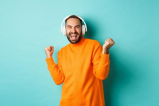 주황색 스웨터에 행복 한 성인 남자를 찾고 파란색 배경 위에 서 헤드폰에서 음악을 듣고.