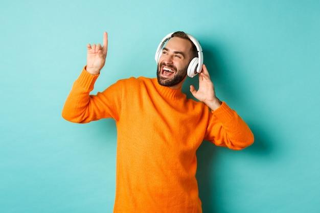 Felice uomo adulto in maglione arancione, guardando in alto e ascoltando musica in cuffia in piedi contro il muro turchese
