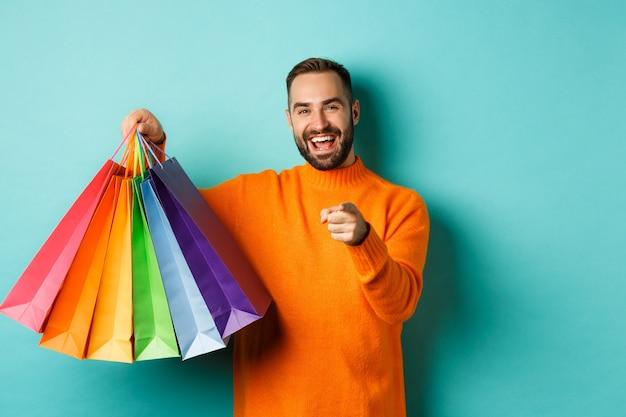 행복 한 성인 남자 카메라에서 손가락을 가리키는, 쇼핑백을 들고 웃 고