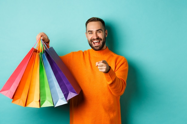 Happy adult man pointing finger at camera, holding shopping bags and smiling