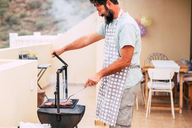 친구가 함께 재미를 위해 집에서 그릴 바베큐와 함께 고기를 요리하는 수염을 가진 행복한 성인 남자