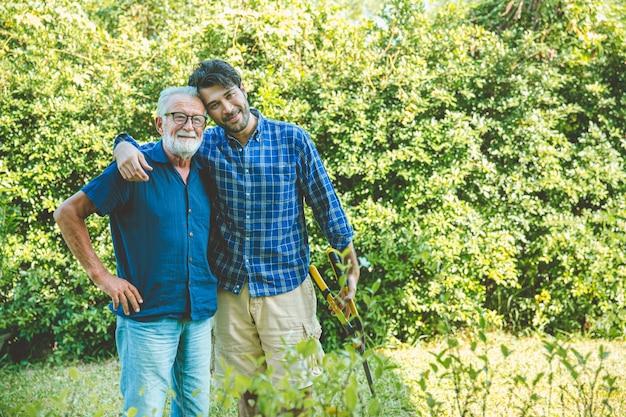노인이 있는 행복한 성인 남자는 집에서 가꾸는 정원을 가꾸며 함께 사는 초상화 미소를 짓습니다.