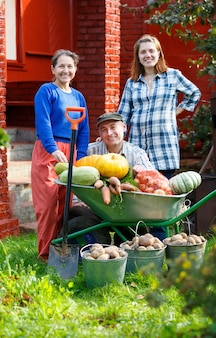 Happy adult men and women with a great harvest in the outdoor garden