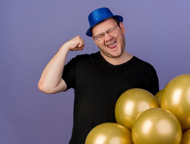 Happy adult slavic man in optical glasses wearing blue party hat raises fist up standing with helium balloons