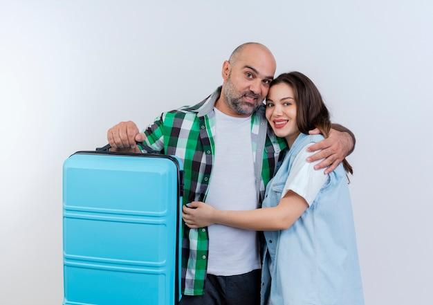 幸せな大人の旅行者カップルの男が探しているお互いを抱き締めるスーツケースを持っています