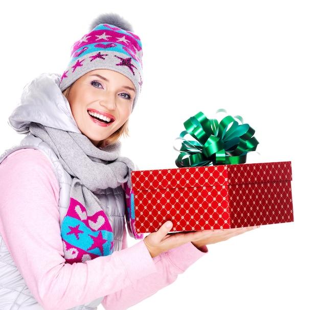 Счастливая взрослая женщина дает рождественский подарок в зимней верхней одежде, изолированной на белом