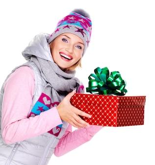 白で隔離の冬のアウターウェアでクリスマスプレゼントを与える幸せな大人の女性