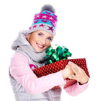 幸せな大人の女性は白で隔離の冬のアウターウェアで赤いクリスマスボックスギフトを保持します
