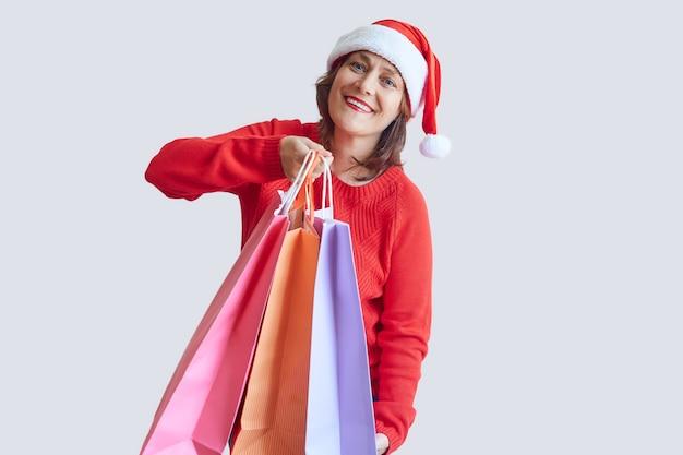 彼女の手にカラフルな買い物袋を持つサンタ帽子の幸せな大人の女性
