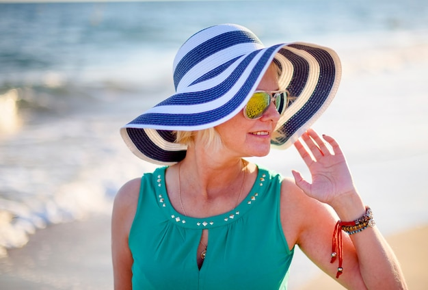 Счастливая взрослая женщина в солнечных очках и полосатой шляпе наслаждается летними каникулами на пляже.
