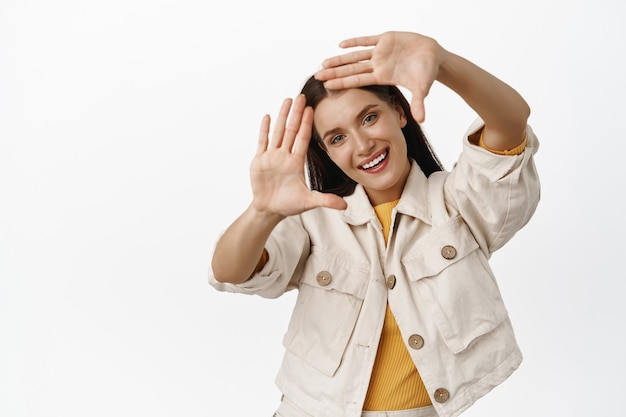 Happy adult woman smiling, looking through hand frames and tilt head, measure angle, imaging perfect shot, getting creative, standing in casual clothes on white