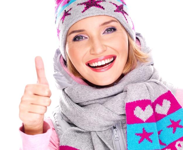 Felice donna adulta in abiti invernali con luminose emozioni positive mostra i pollici in su segno isolato su bianco