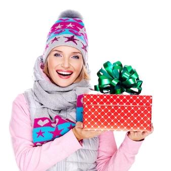 Donna adulta felice con un regalo in un capospalla invernale isolato su bianco