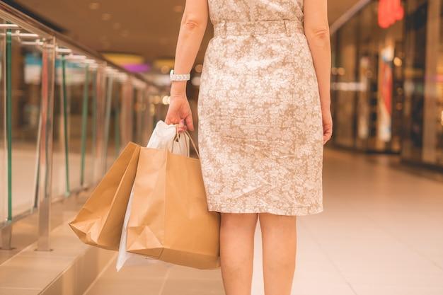 슈퍼마켓에서 쇼핑 봉투와 함께 행복 한 성인 여자