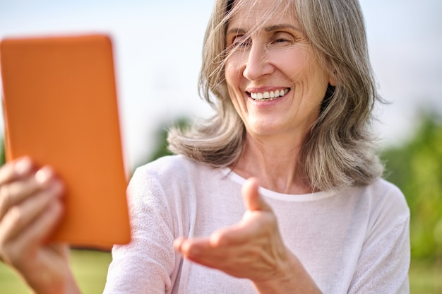 Happy adult woman with tablet in outstretched hand