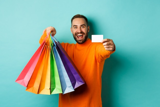 Happy aduly man showing credit card and shopping bags, standing against turquoise background