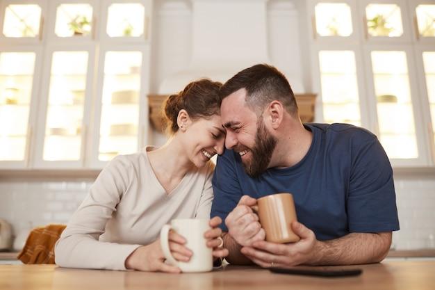 행복한 다정한 젊은 백인 부부는 식탁에 기대어 커피를 마시며 웃고 있습니다...