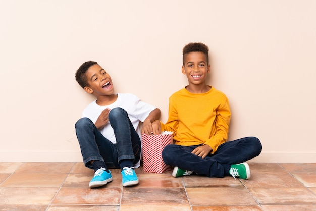 Happy african american brothers  holding popcorns