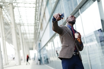 Happy African American business man dances while he listens to the music