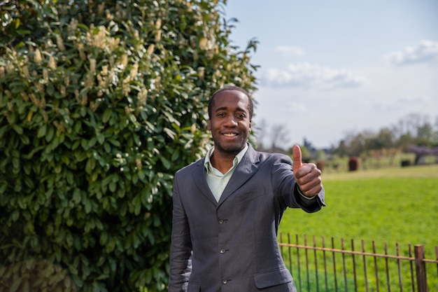 Happy african american businessman makes a thump up gesture outdoor.