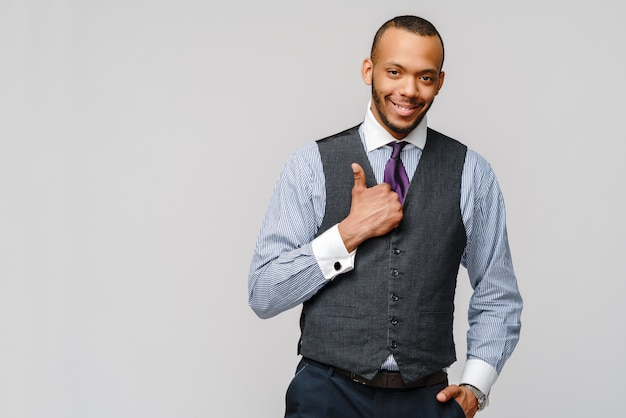 Happy african-american businessman showing his thumb up with smile over grey wall
