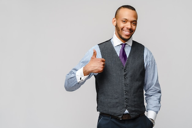 灰色の壁を越えて笑顔で彼の親指を現して幸せなアフリカ系アメリカ人のビジネスマン