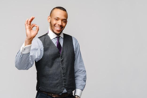 灰色の壁に笑顔でokの標識を示す幸せなアフリカ系アメリカ人のビジネスマン