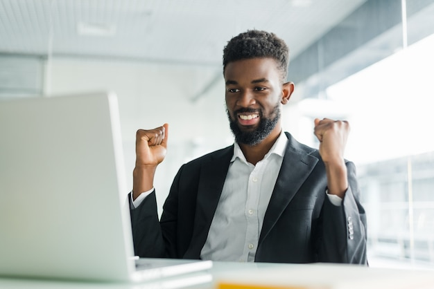 Happy african-american businessman in suit looking at laptop excited by good news online. black man winner sitting at office desk achieved goal raising hands celebrating business success win result